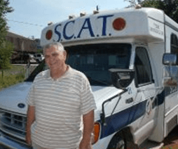 Man in white shirt standing in front of a SCAT bus.